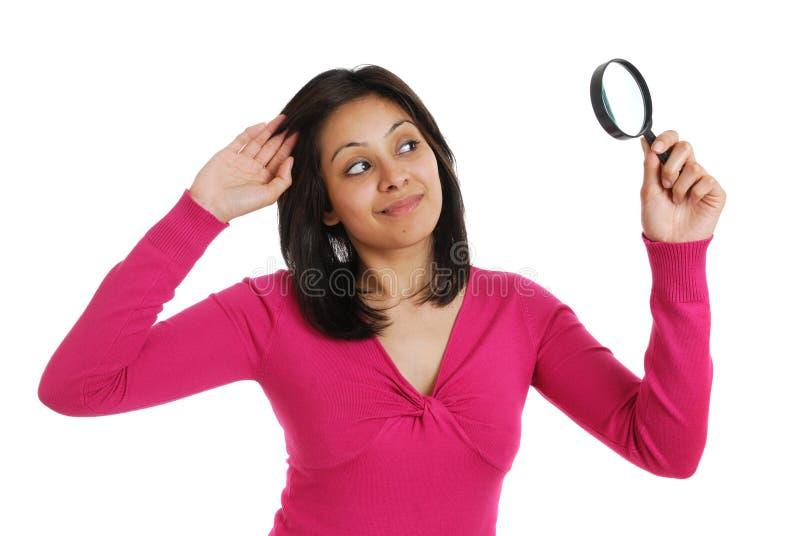 Estudante fêmea que olha através de uma lupa fotografia de stock royalty free