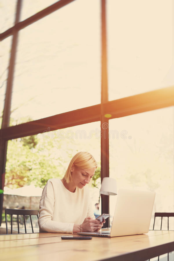 Estudante fêmea que senta-se na tabela de madeira da biblioteca da universidade moderna, filtro fotos de stock