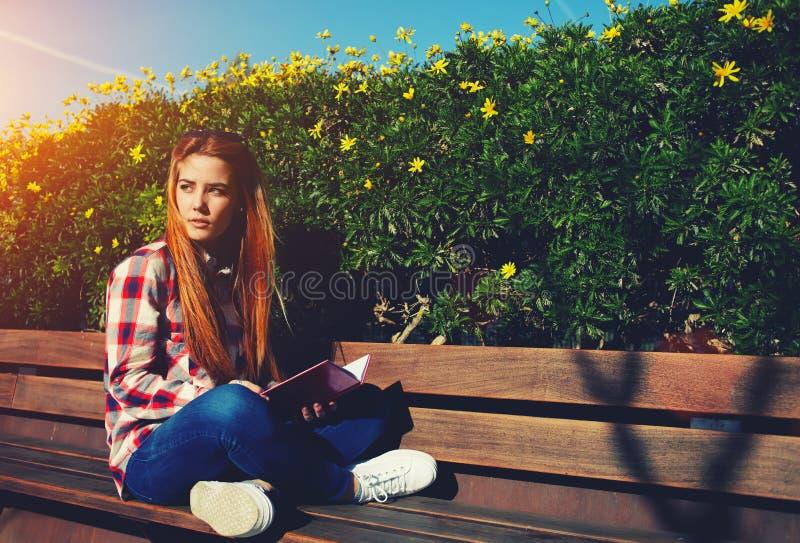 Estudante fêmea que senta-se no banco de madeira no terreno imagens de stock
