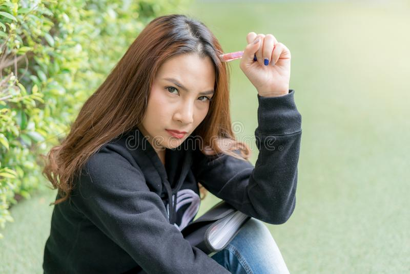 Estudante fêmea que senta-se no banco do gramado no terreno fotos de stock