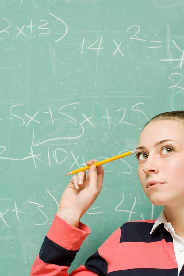 Estudante fêmea que tenta resolver a fórmula foto de stock