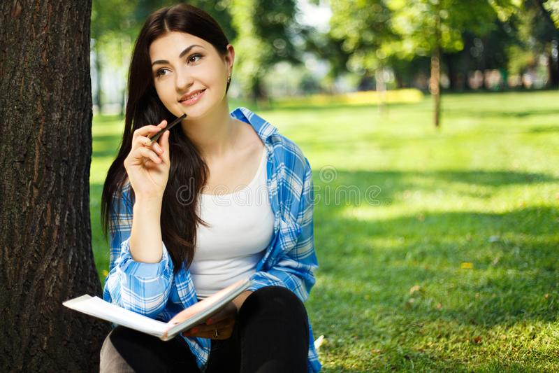 Estudante fêmea que toma notas em seu caderno Assento da mulher nova fotografia de stock royalty free