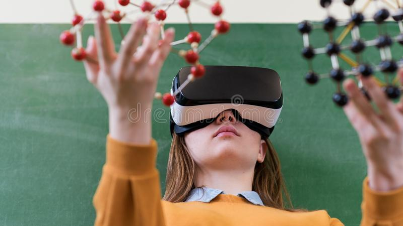 Estudante fêmea que veste os vidros da realidade virtual, guardando o modelo de estrutura molecular Classe da ciência, educação,  imagens de stock