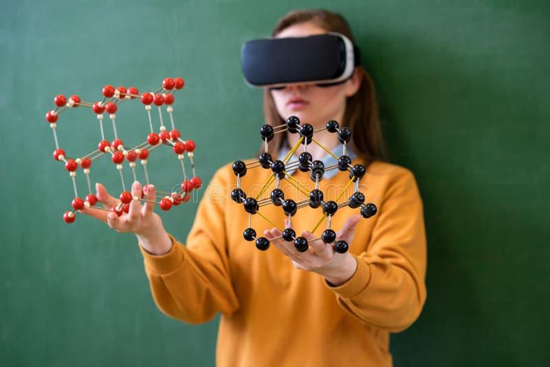 Estudante fêmea que veste os vidros da realidade virtual, guardando o modelo de estrutura molecular Classe da ciência, educação,  foto de stock
