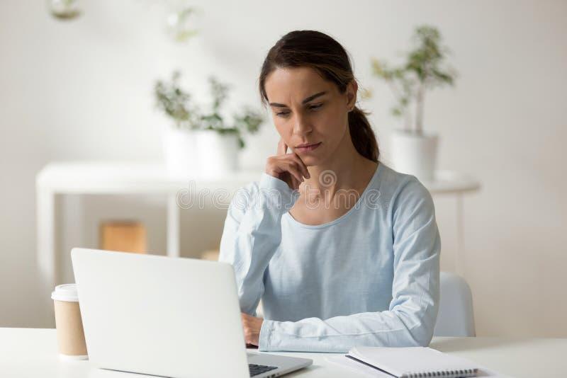 Estudante fêmea sério que usa o portátil, trabalhando no projec difícil fotos de stock royalty free