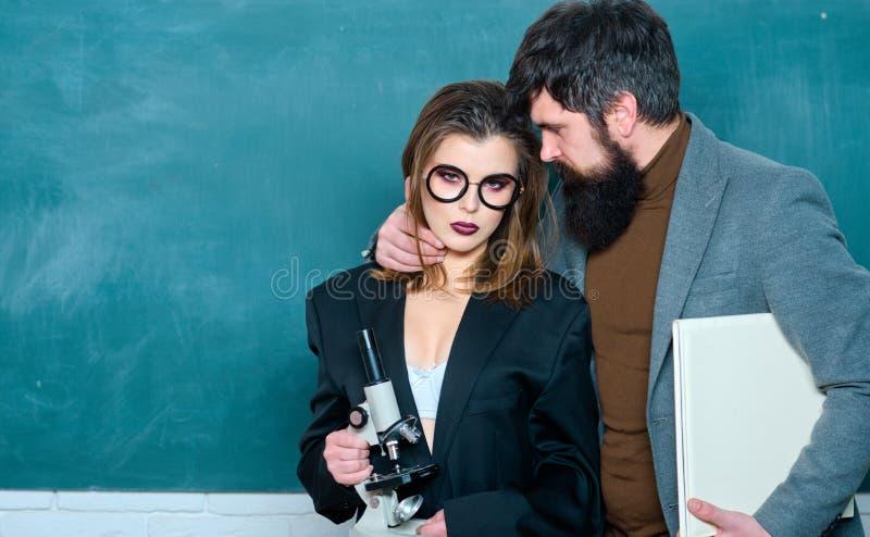 Estudante fêmea 'sexy' que aponta no quadro Romance do local de trabalho do homem consider?vel e da mulher 'sexy' na universidade imagens de stock