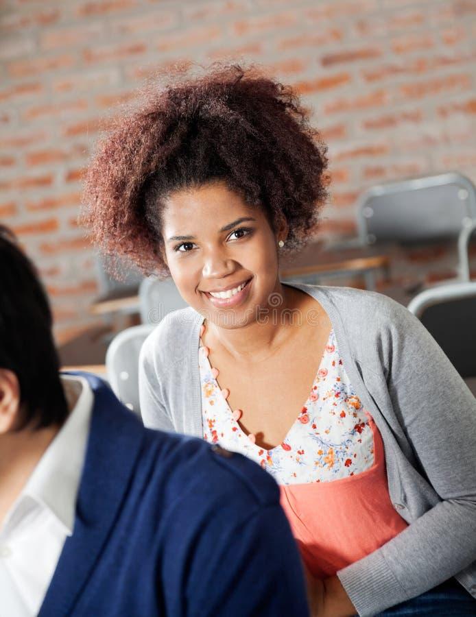 Estudante fêmea Sitting With Classmate na sala de aula imagem de stock royalty free