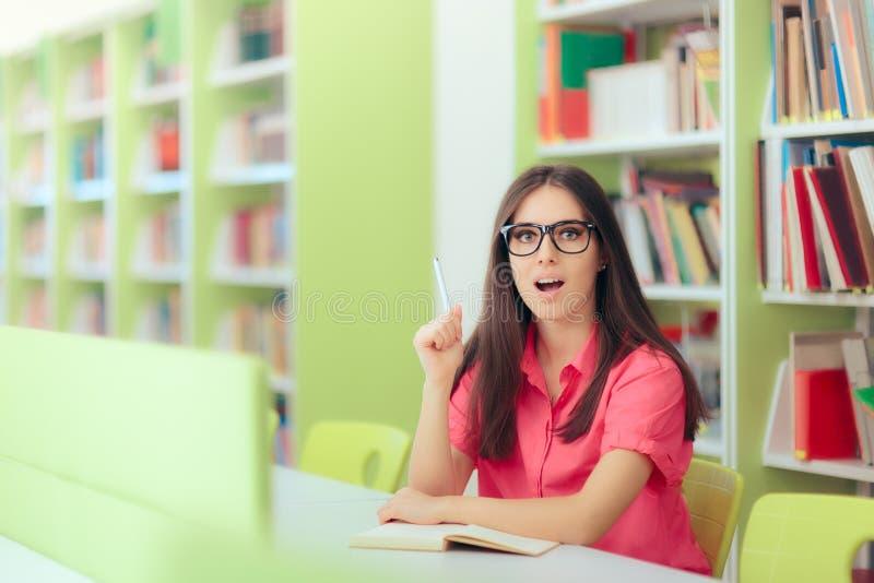 Estudante fêmea Studying e notas da tomada na biblioteca fotografia de stock royalty free