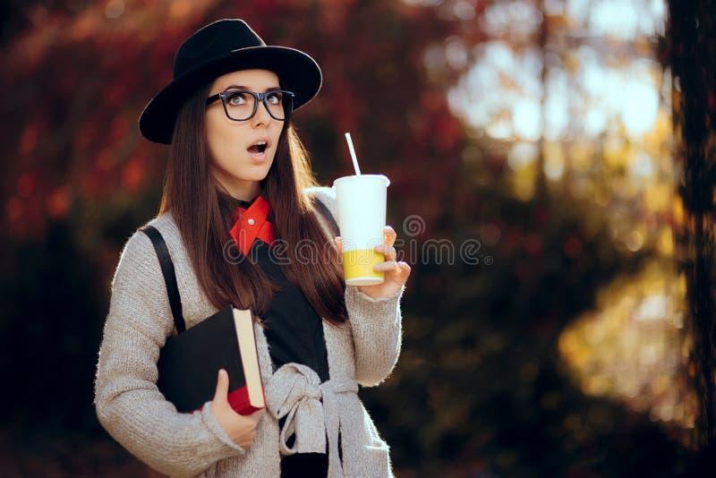 Estudante fêmea surpreendido Holding uma bebida quente e um livro fotografia de stock