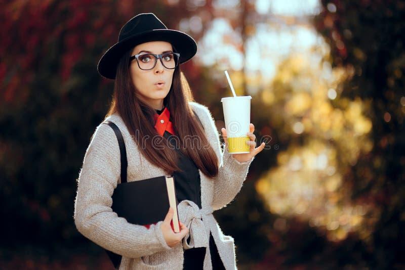 Estudante fêmea surpreendido Holding uma bebida quente e um livro imagem de stock royalty free