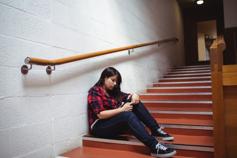 Estudante fêmea virado que senta-se na escadaria fotografia de stock