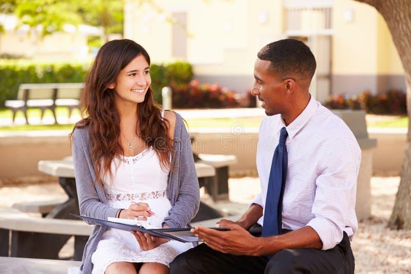 Estudante fêmea With Work de Sitting Outdoors Helping do professor fotografia de stock