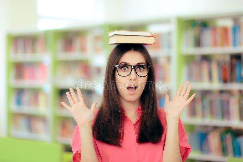 Estudante fêmea Writing uma atribuição do ensaio na biblioteca escolar imagens de stock