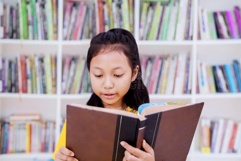 Estudante f?mea que l? um livro na biblioteca fotos de stock