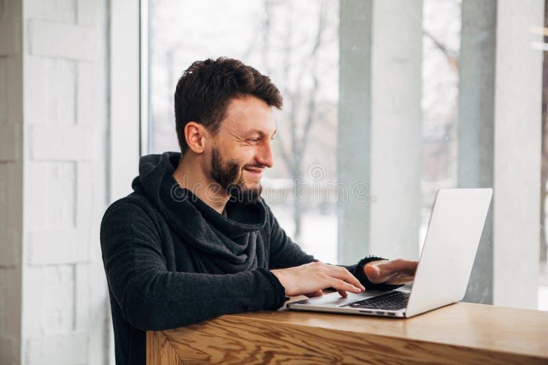 Estudante farpado novo feliz que mantém suas mãos no teclado do laptop genérico ao trabalhar no projeto do diploma fotos de stock royalty free