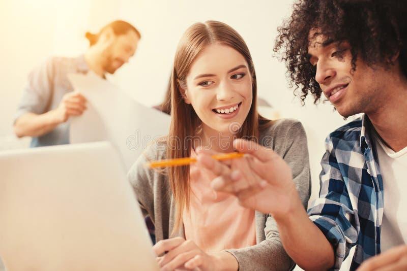 Estudante feliz e seu noivo que olham a tela de um portátil foto de stock