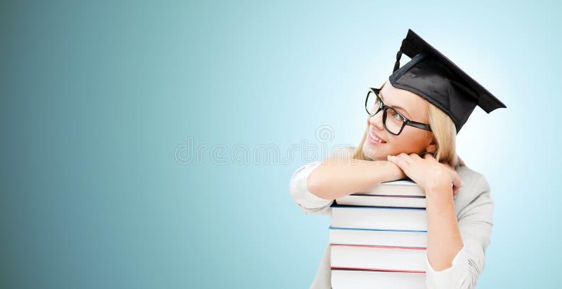 Estudante feliz no tampão da placa do almofariz com livros imagem de stock royalty free