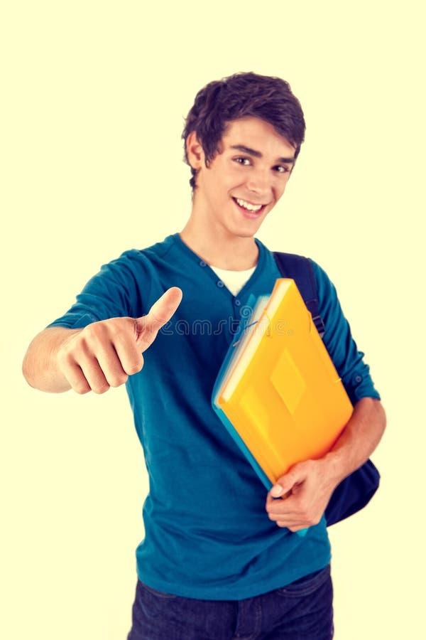 Estudante feliz novo que mostra os polegares acima imagem de stock royalty free