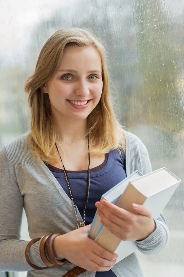 Estudante feliz que guarda livros pela janela fotografia de stock royalty free