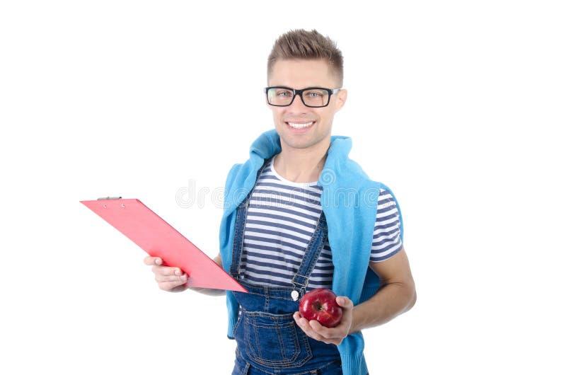 Estudante feliz que guarda uma prancheta e uma maçã fotos de stock royalty free