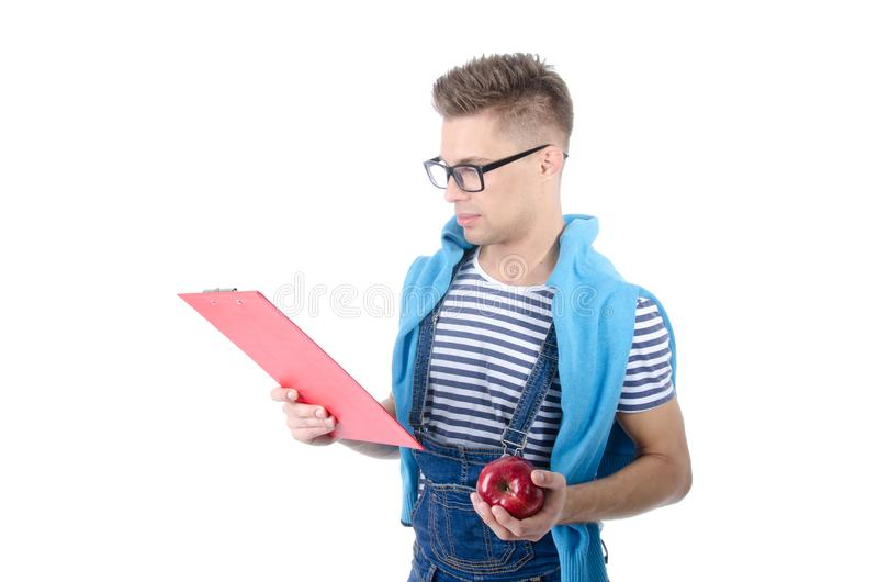 Estudante feliz que guarda uma prancheta e uma maçã fotos de stock