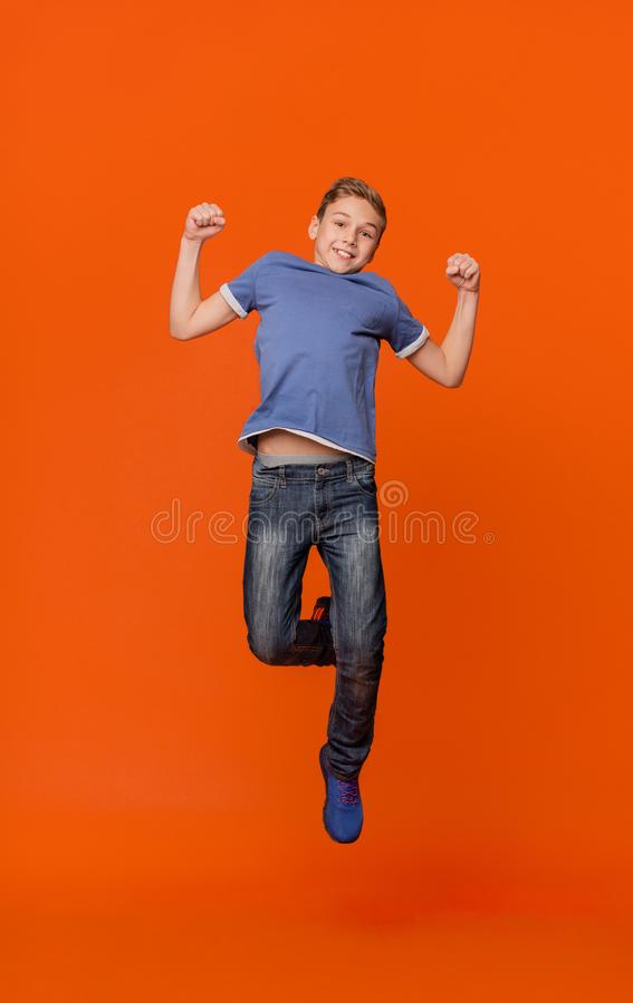 Estudante feliz que salta para a alegria na laranja fotografia de stock