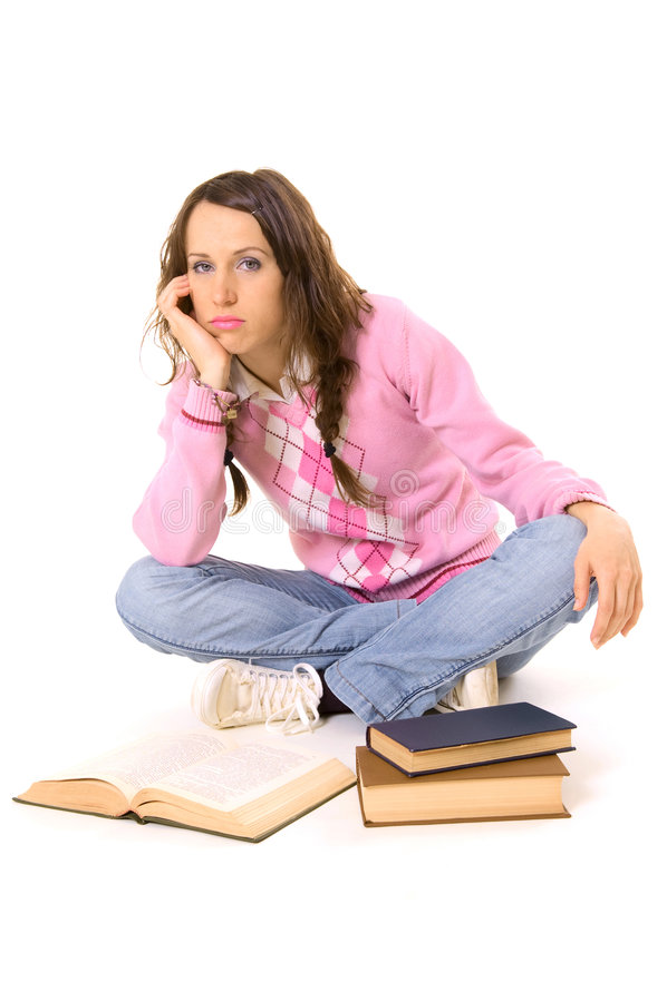 Estudante furado que senta-se no assoalho com livros fotografia de stock