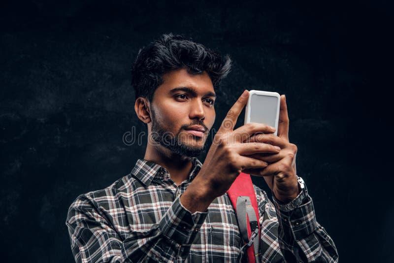 Estudante indiano considerável com trouxa que conversa com seus amigos que usam um smartphone foto de stock