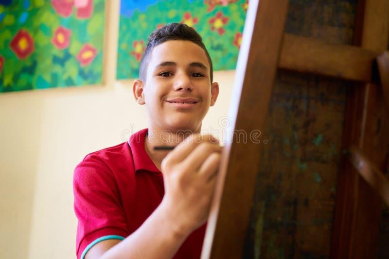 Estudante latino-americano feliz Of Art School Smiling At Camera do menino imagens de stock