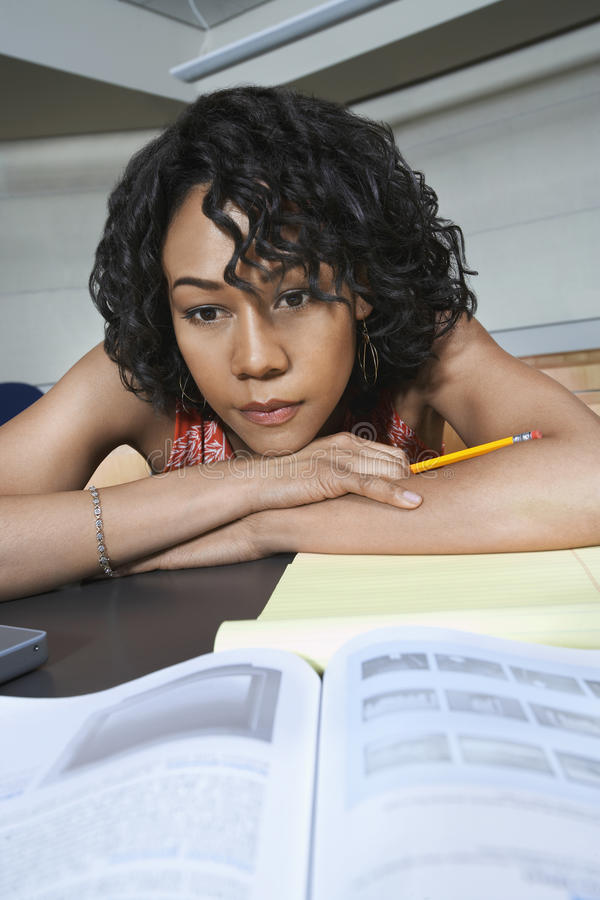 Estudante Looking At Book na mesa imagens de stock royalty free