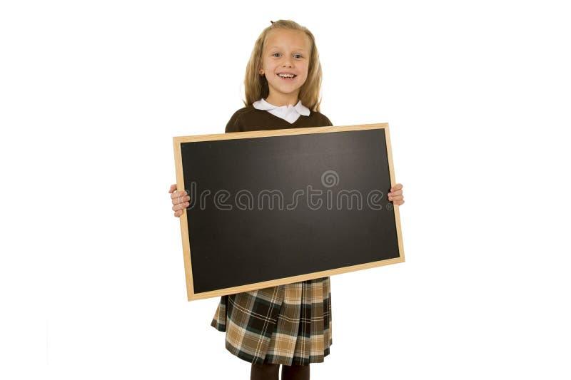 Estudante loura bonita pequena que sorri quadro-negro vazio pequeno feliz e alegre da terra arrendada e da exibição fotos de stock