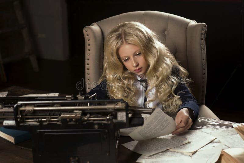 A estudante loura encaracolado de cabelos compridos bonita aprende tiredly o hom fotografia de stock royalty free