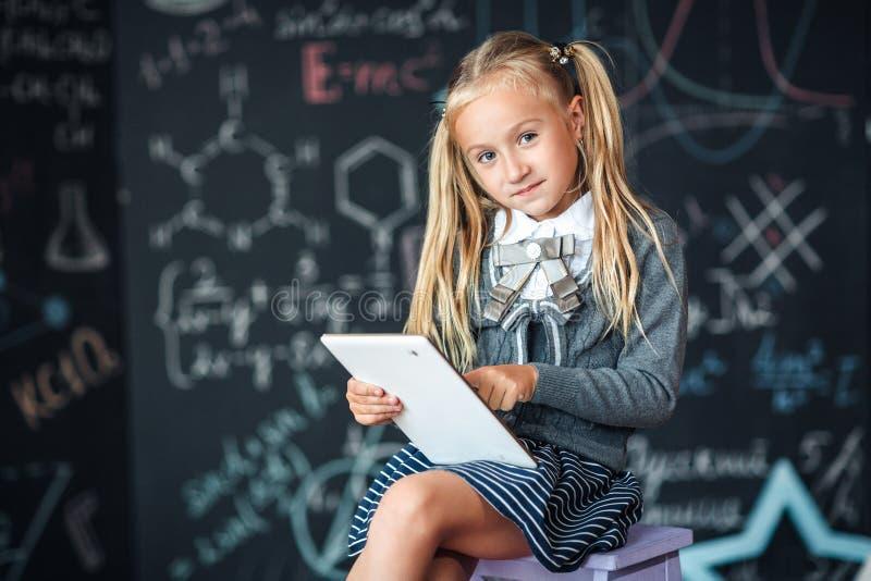 Estudante loura pequena adorável na farda da escola que guarda a tabuleta digital branca Quadro com fundo das fórmulas da escola  fotos de stock royalty free