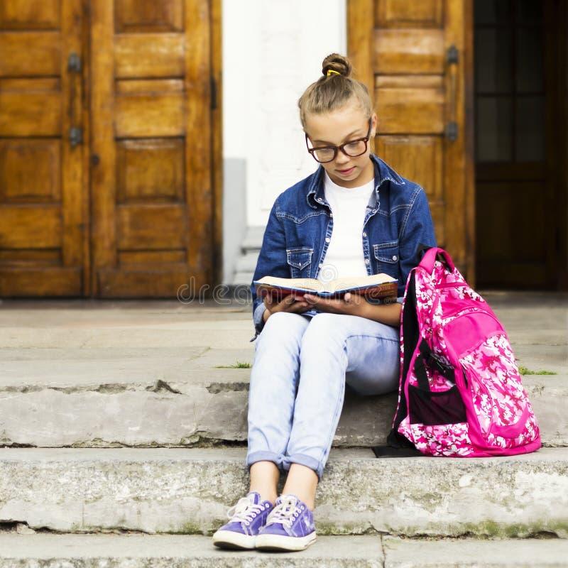 Estudante louro bonito da menina que lê um livro ao sentar-se perto da escola Educação imagem de stock