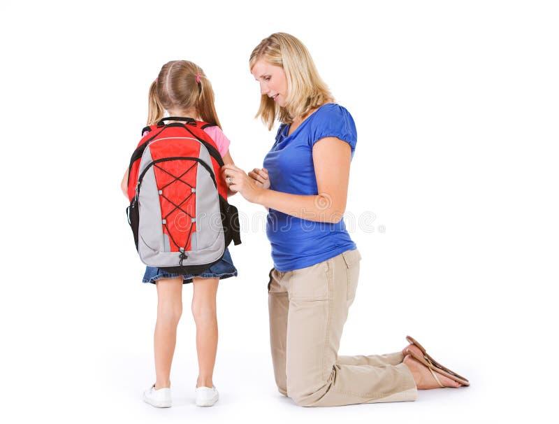 Estudante: A mãe ajuda a menina com zíper da trouxa fotos de stock