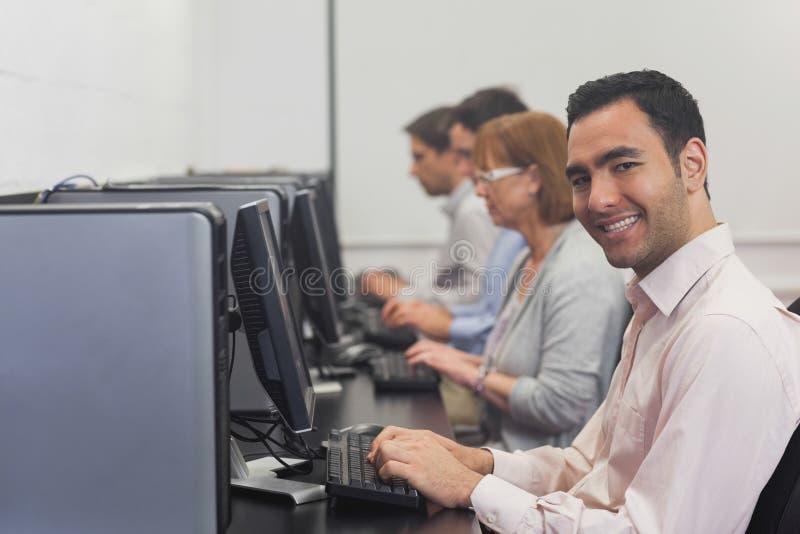 Estudante maduro alegre que senta-se na classe do computador fotos de stock royalty free