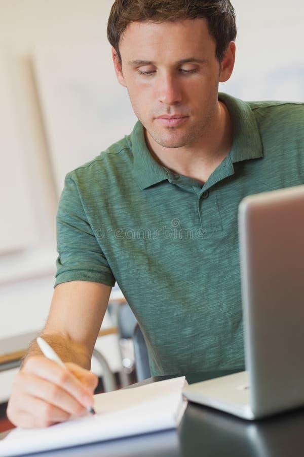 Estudante maduro considerável que senta-se na sala de aula ao aprender concentrada imagem de stock royalty free