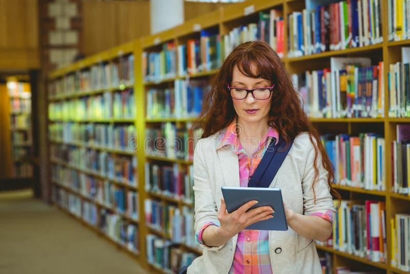 Estudante maduro na biblioteca usando a tabuleta imagem de stock royalty free