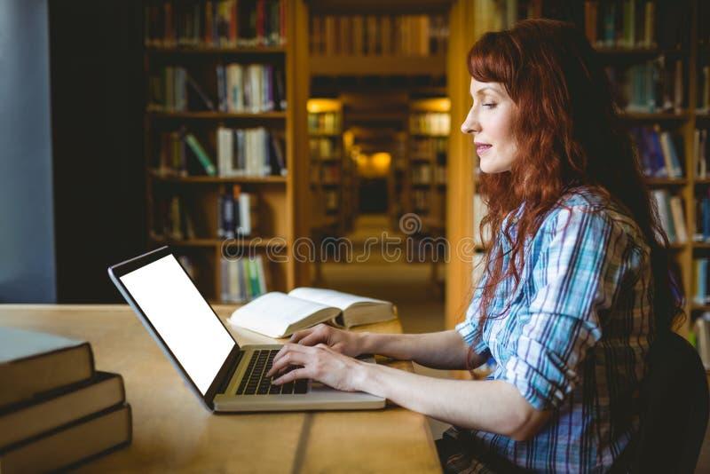 Estudante maduro que estuda na biblioteca foto de stock