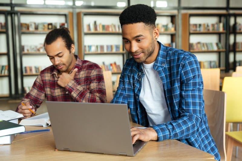 Estudante masculino africano de sorriso dos jovens que usa o portátil para um estudo foto de stock royalty free