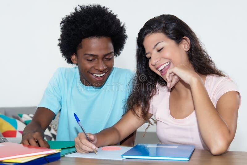 Estudante masculino afro-americano que aprende com o stu fêmea caucasiano imagem de stock royalty free