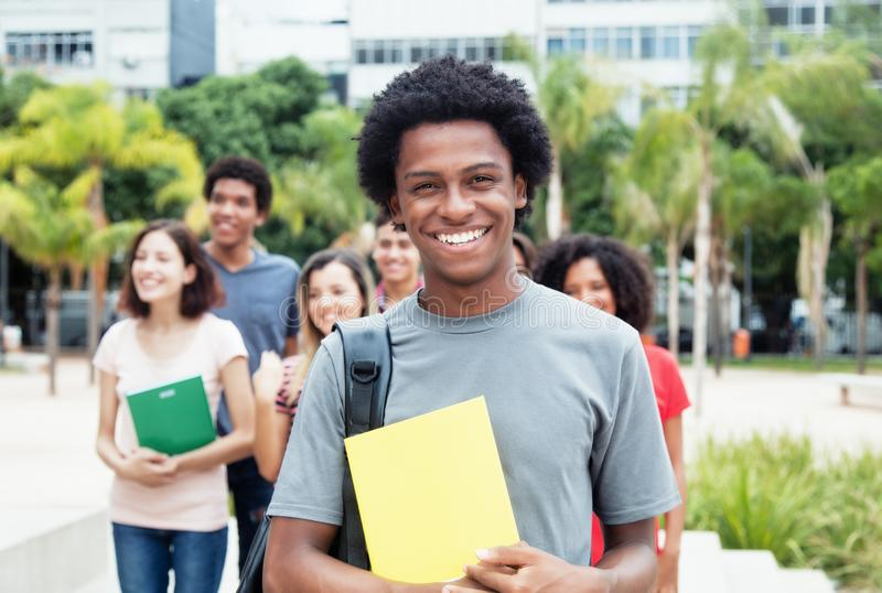 Estudante masculino afro-americano que mostra o polegar com grupo de interno fotos de stock