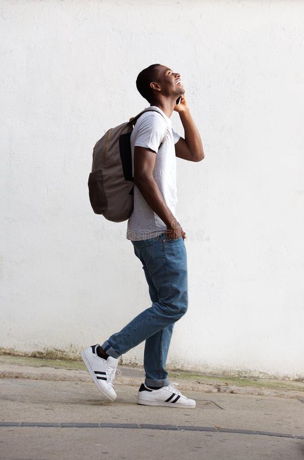 Estudante masculino alegre que anda e que fala no telefone celular imagem de stock royalty free