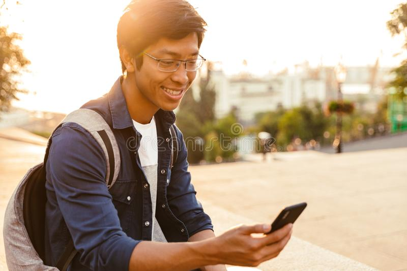 Estudante masculino asiático alegre nos monóculos usando o smartphone imagens de stock
