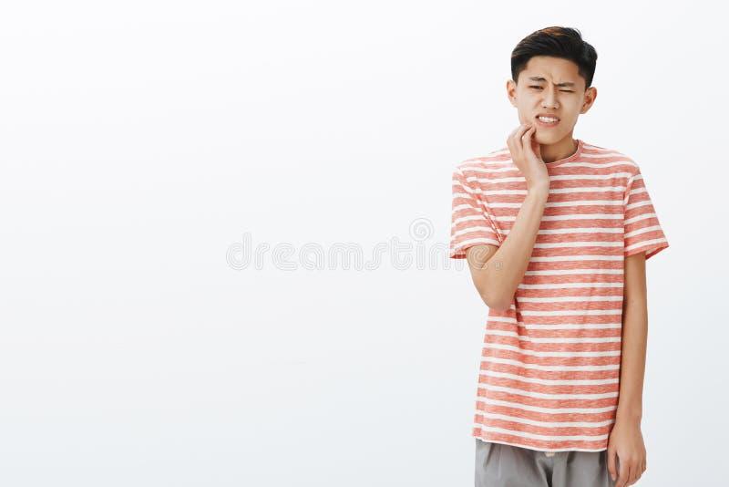 Estudante masculino asiático novo atrativo inquieto que tem mordente tocante da deterioração de dente que reage na dor, tendo os  fotografia de stock royalty free