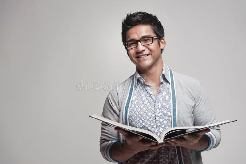 Estudante masculino asiático que prende um livro fotografia de stock