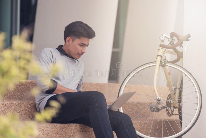 Estudante masculino asiático que senta-se nas escadas e que sorri como o lapt do uso fotografia de stock royalty free