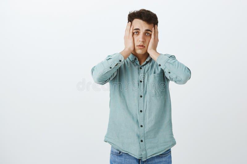 Estudante masculino cansado desesperado na camisa ocasional, guardando as mãos na cabeça e em olhar fixamente descuidadas na câme foto de stock