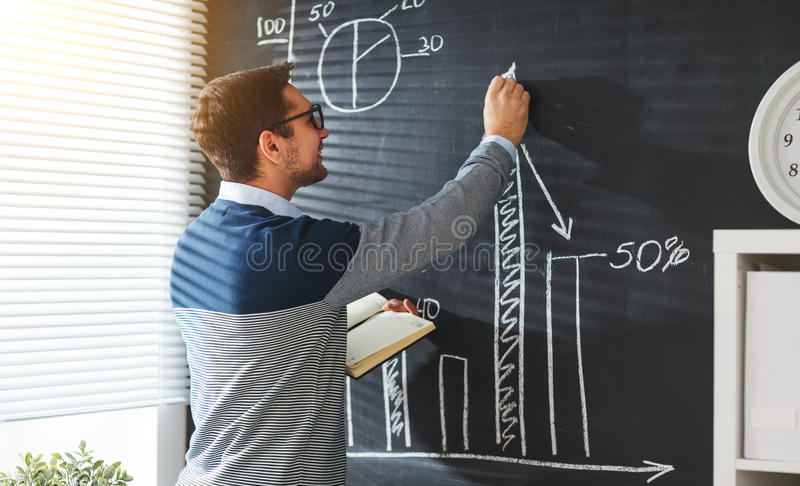 Estudante masculino feliz, professor, freelancer com giz no quadro-negro imagem de stock royalty free