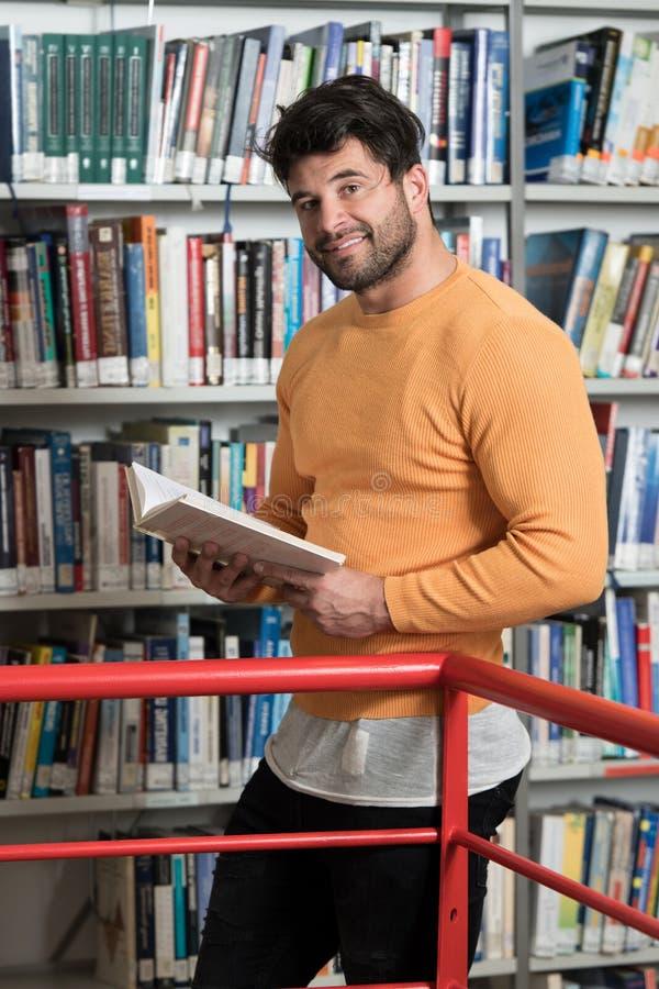 Estudante masculino feliz Reading do livro na biblioteca imagem de stock royalty free